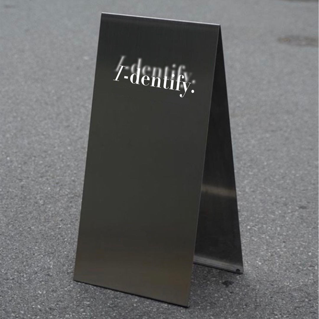 Banner image for Identify exhibition showing a black card folded in half with Identify printed on it
