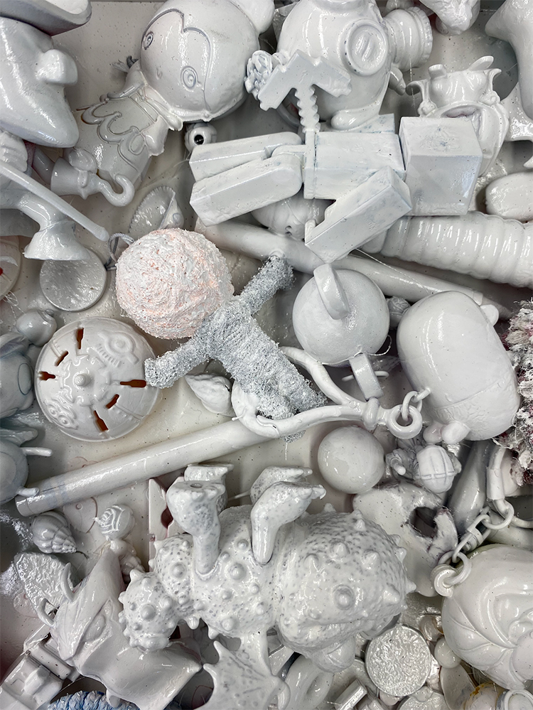 A series of small objects that have been covered in white paint are clustered together