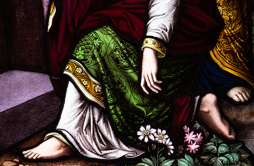 Image of a stained glassed window showing a hand and foot